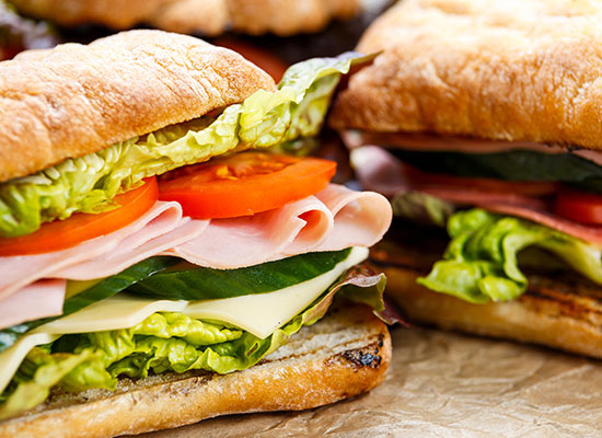 Fresh sub sandwiches with tomatoes, lettuce, and ham