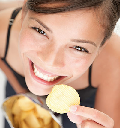 Happy employee eating chips for a snack